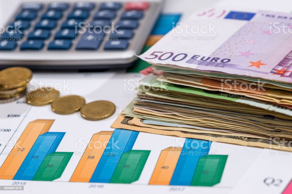euro bills with calculator and pen on financial settlement with the charts. stock photo