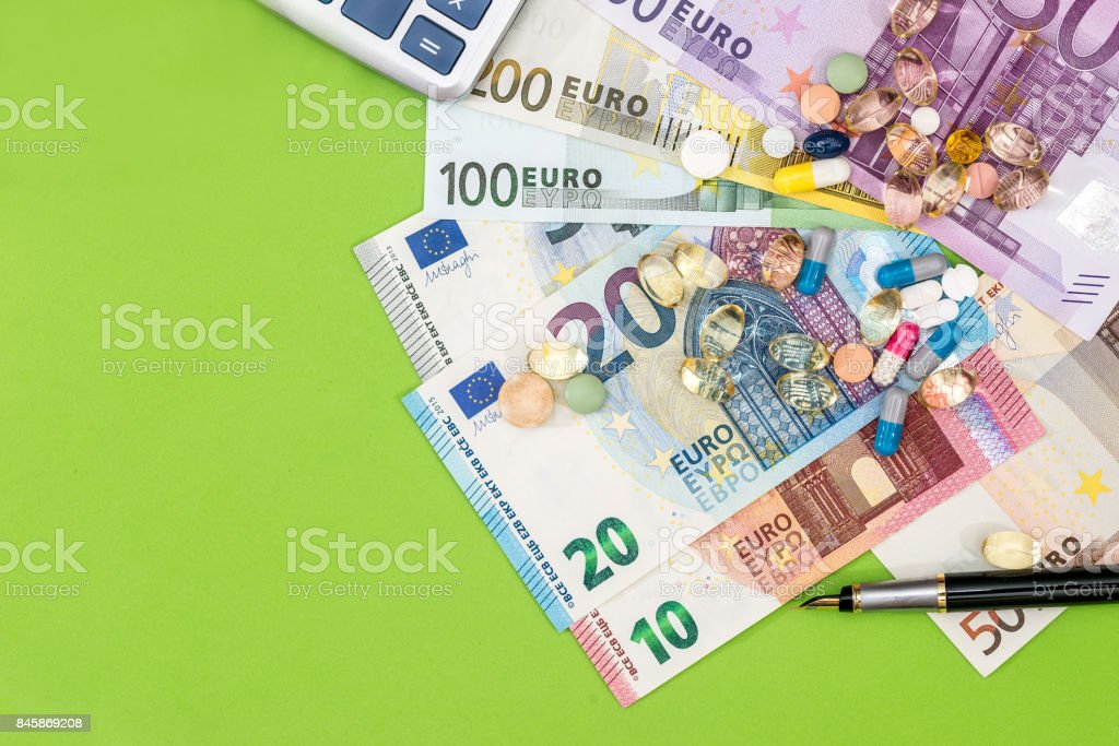 Euro bills with different pills and pen on green stock photo