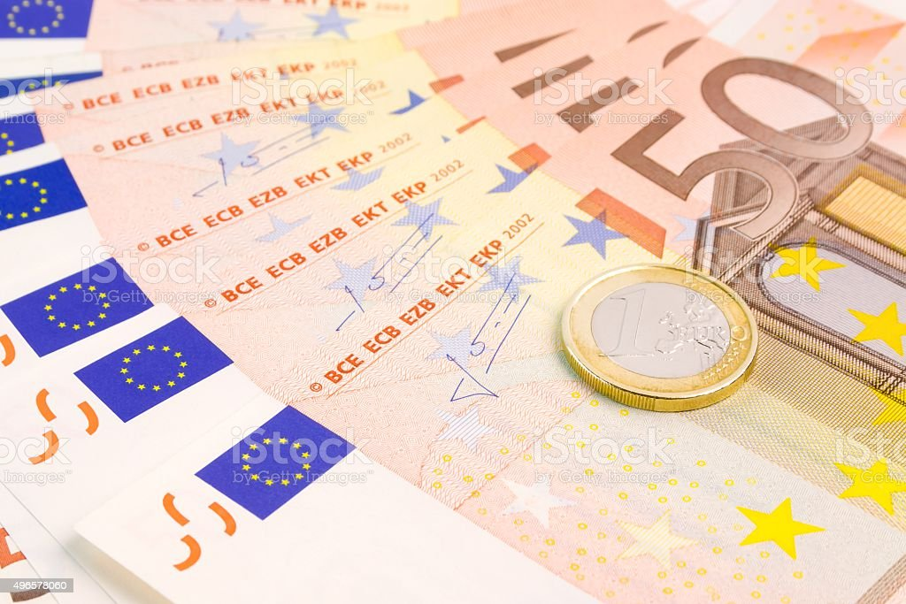 euro coin on 50-euro banknotes stock photo