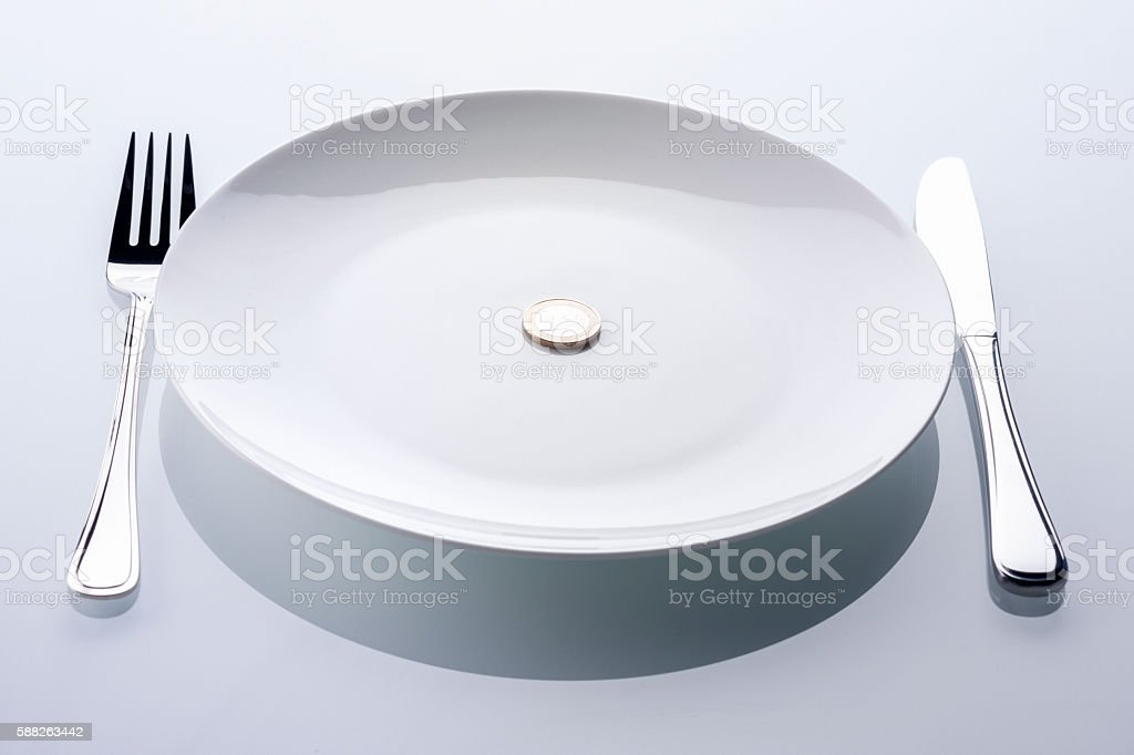 euro coin on empty white plate, symbol for crisis stock photo