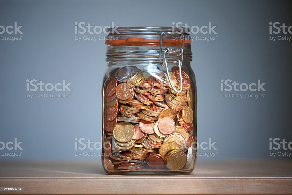 Euro coins in a glass jar stock photo