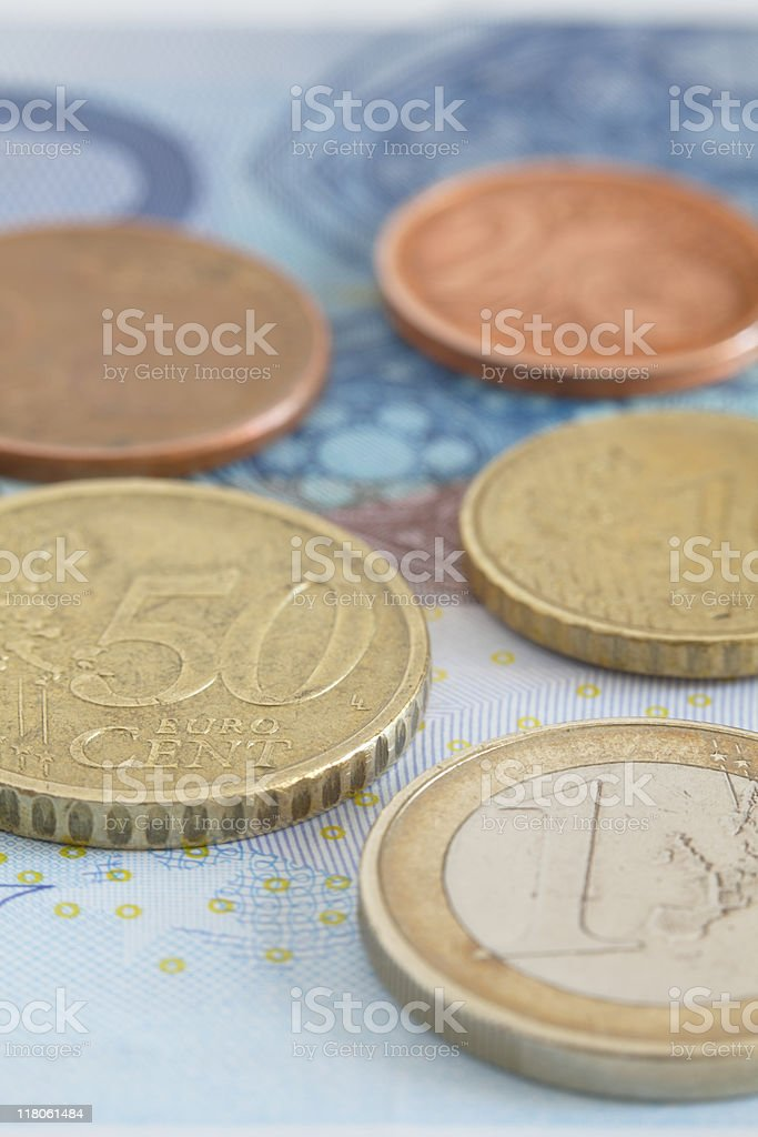 Euro coins on top of a bank note stock photo