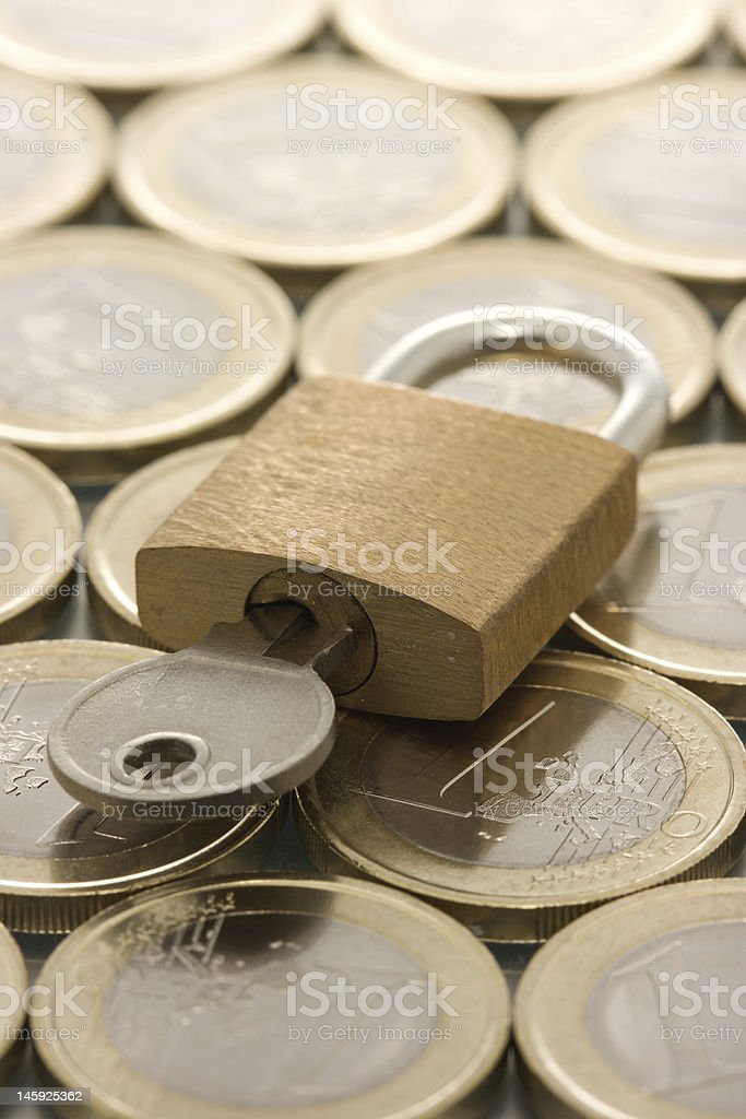 Euro coins pattern and padlock with key royalty-free stock photo