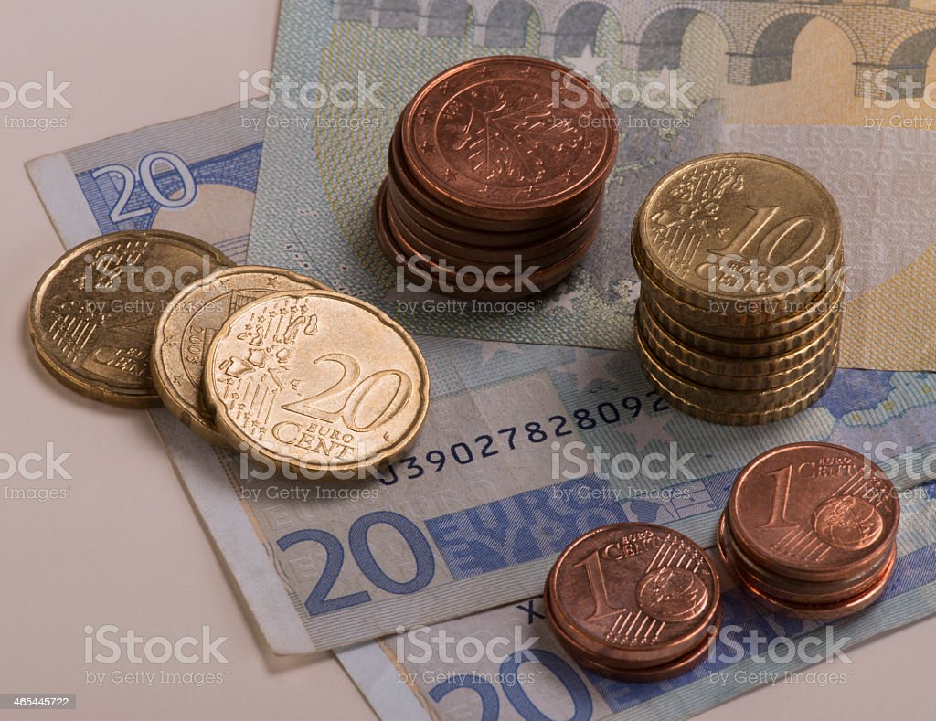 Euro coins stacked on 20 and 5 Euro bills stock photo