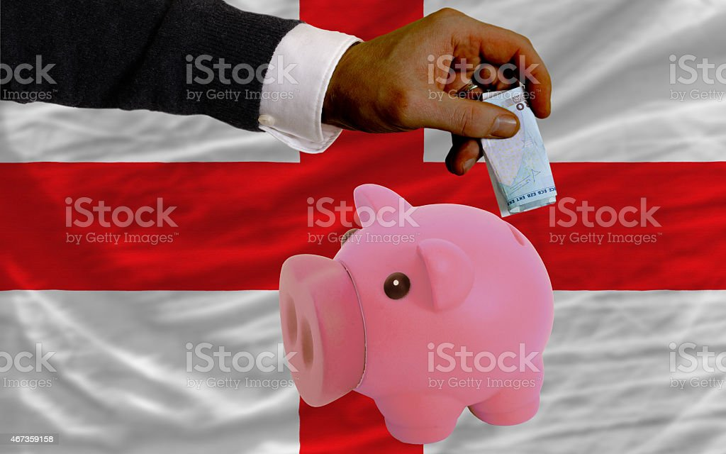 euro into piggy rich bank and flag of england stock photo