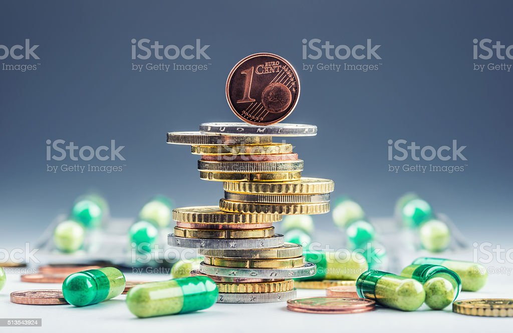 Euro money and medicaments. Eurocoins and pills. Coins stacked on...
