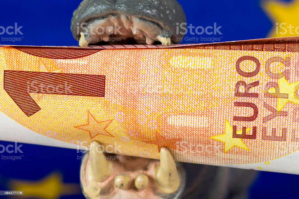10 Euro note in mouth of a hippo figurine stock photo
