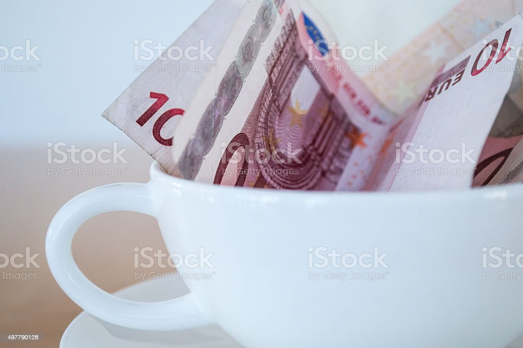 Euro (EUR) Notes in an Empty Coffee Cup Close Up royalty-free stock photo