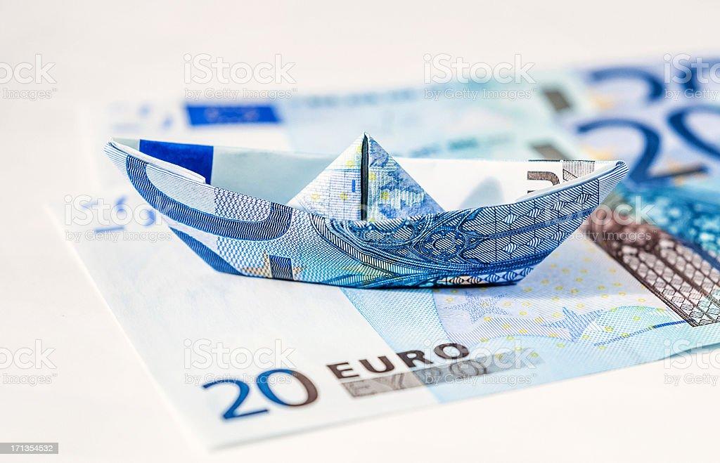 Euro paper boat standing on bills stock photo