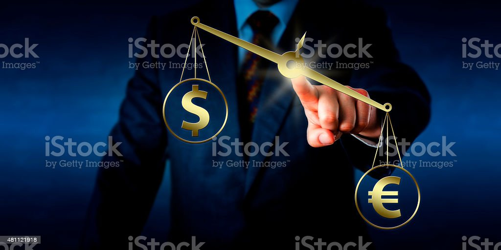 Euro Sign Outweighing The Dollar On Golden Scale stock photo