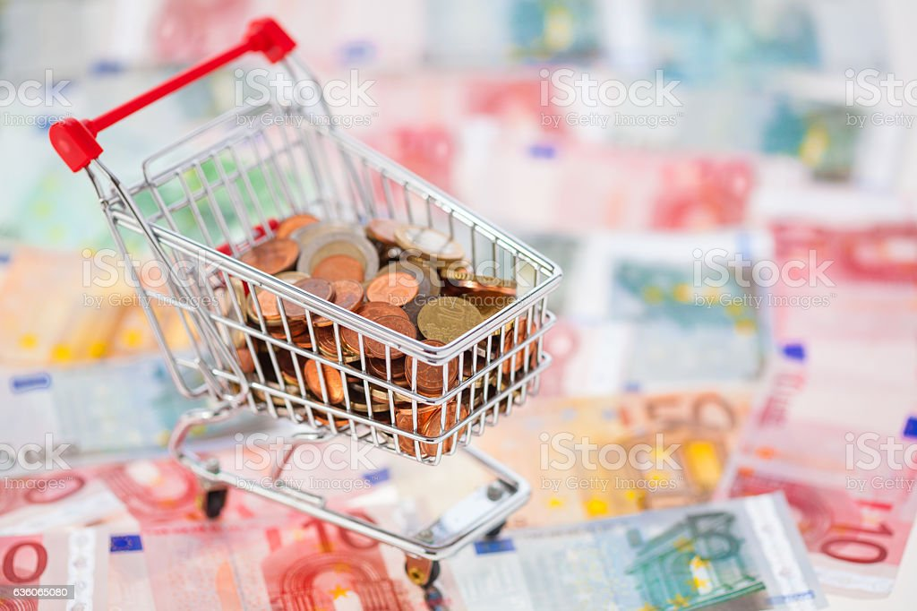 eurocoins in cart on euro notes stock photo