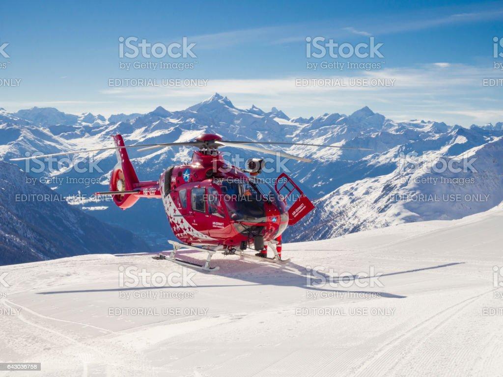 Eurocopter EC135 helicopter of Air Zermatt landed on ski piste stock photo