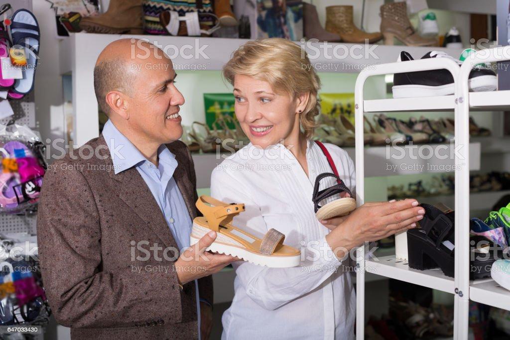 European couple choosing shoes stock photo