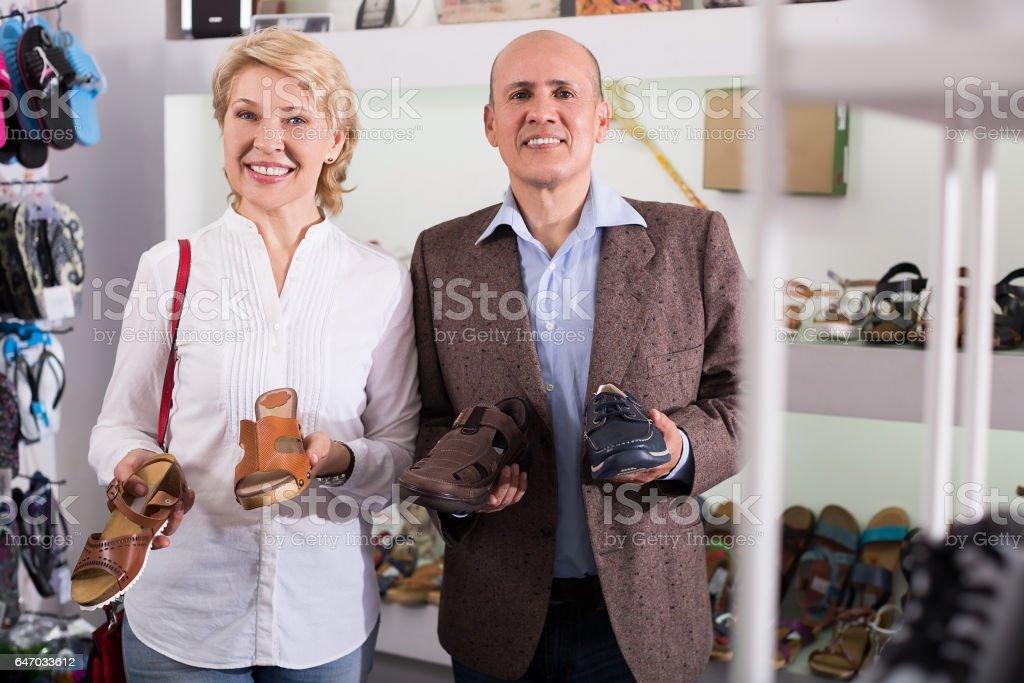 European couple picking shoes stock photo