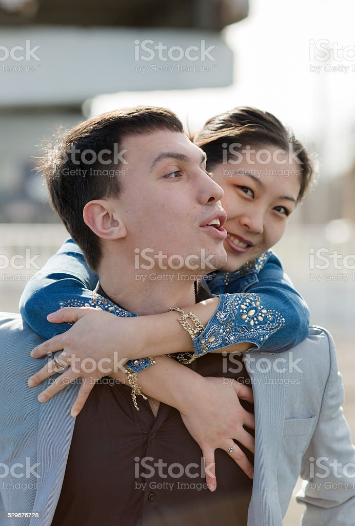 European guy carrying on shoulders his asian girl stock photo