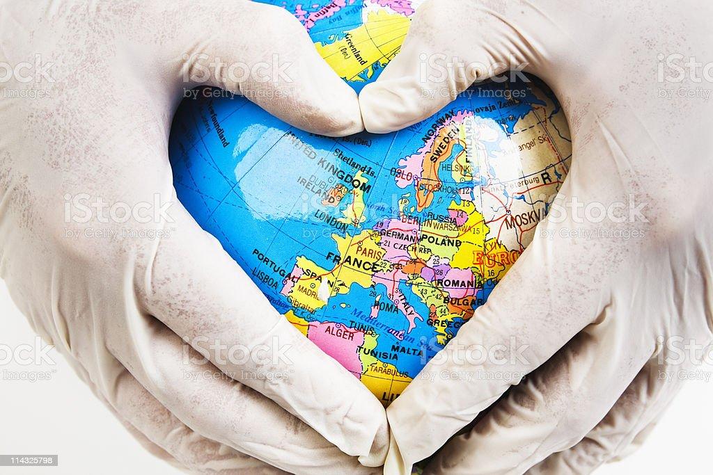 European healthcare: Doctor's hands make heart shape on globe, royalty-free stock photo