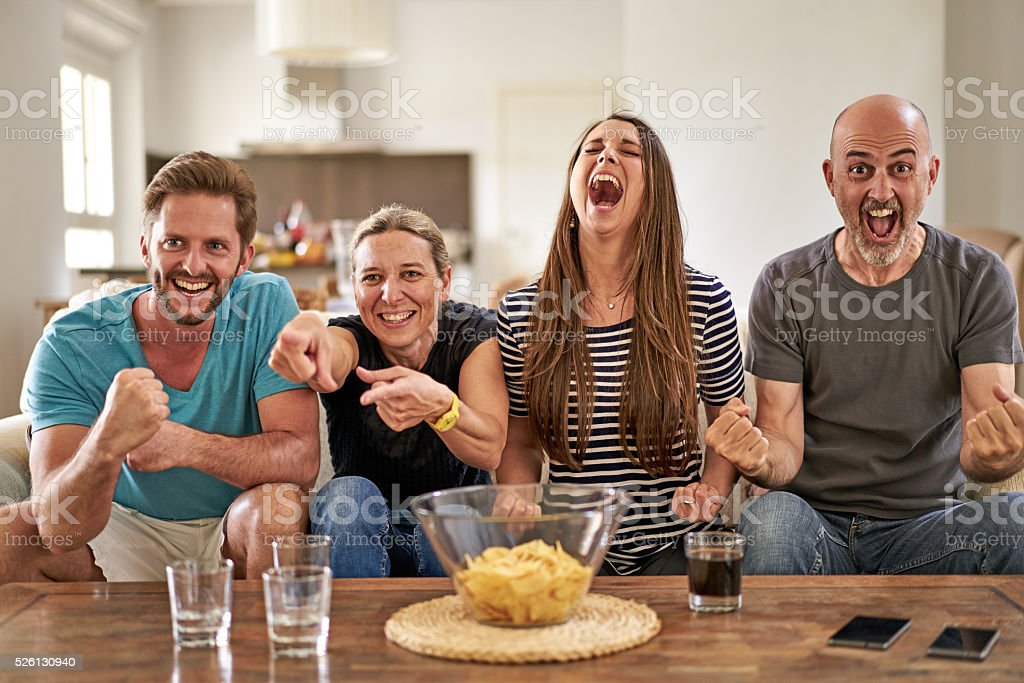 european soccer fans celebrating team on couch in living room stock photo
