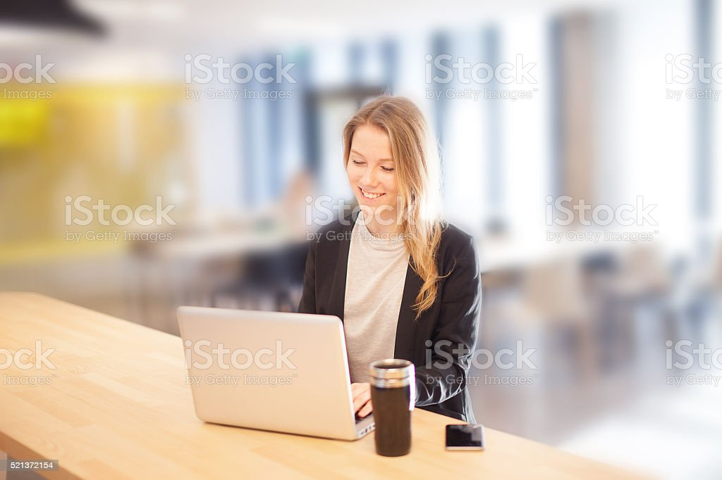 European student sitting at cafeteria with laptop and coffee stock photo