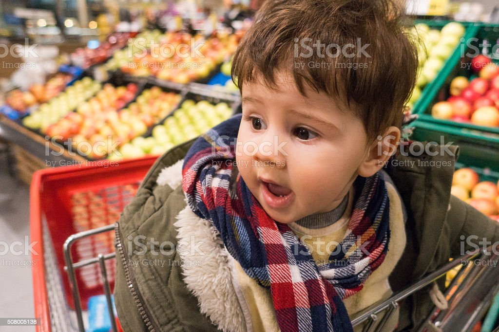 European toddler boy sitting in the shopping cart stock photo