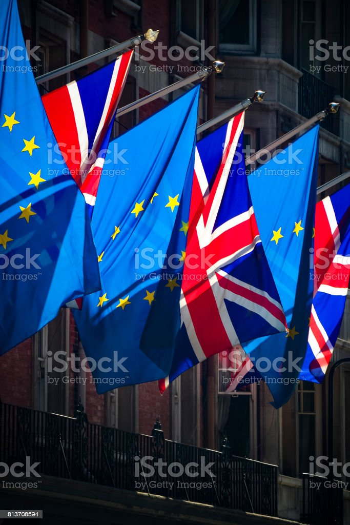 European Union and Union Jack flags in strong sunlight stock photo