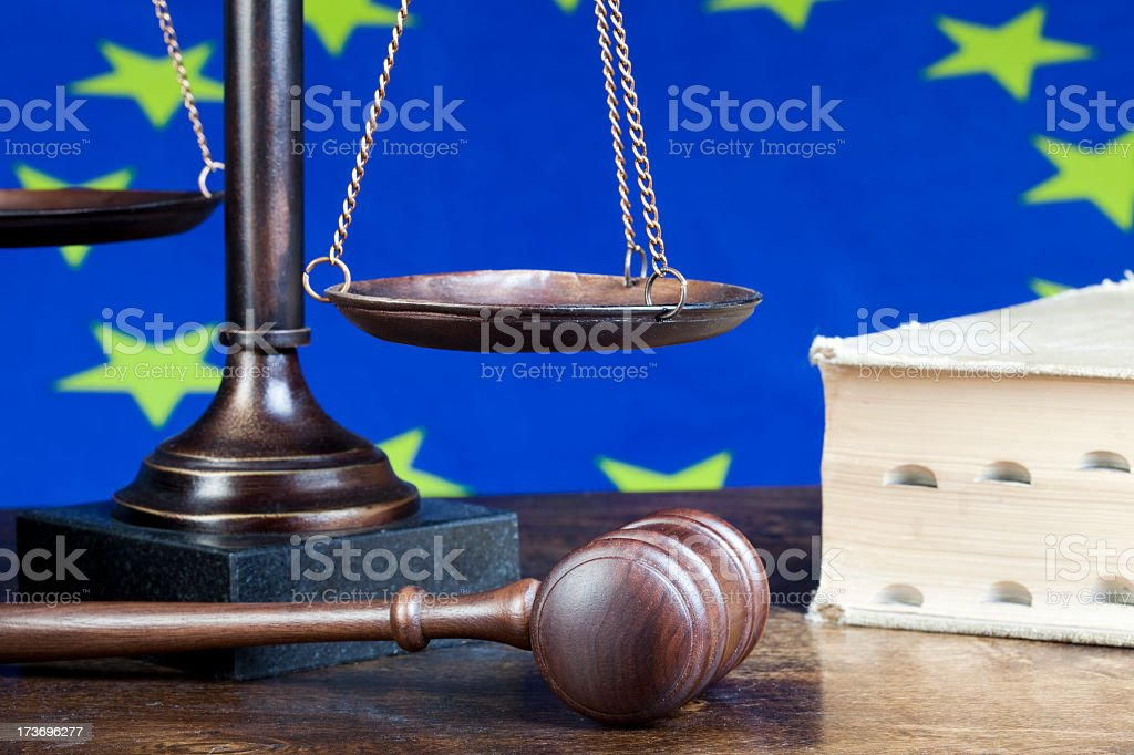 European union flag behind scales and wooden gavel royalty-free stock photo