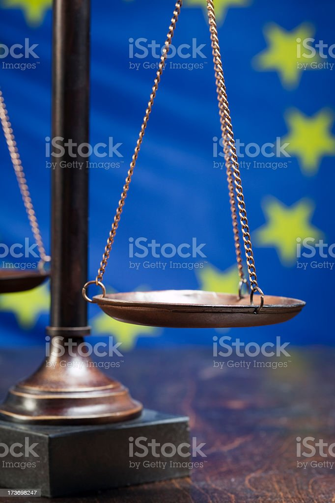European Union flag with scales in foreground royalty-free stock photo
