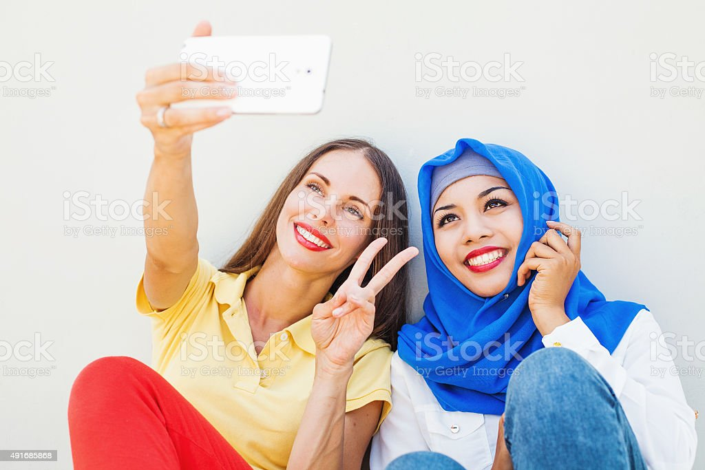 European woman and asian muslim woman making their photo stock photo
