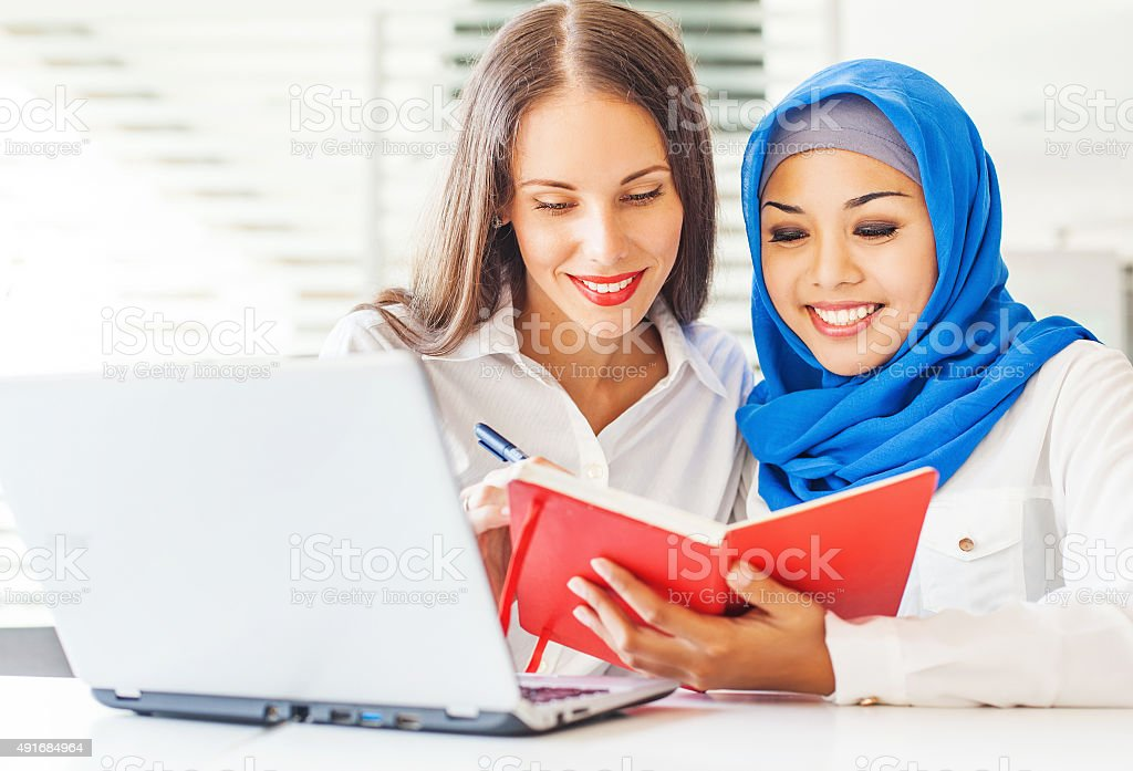 European woman and asian muslim woman working in office stock photo