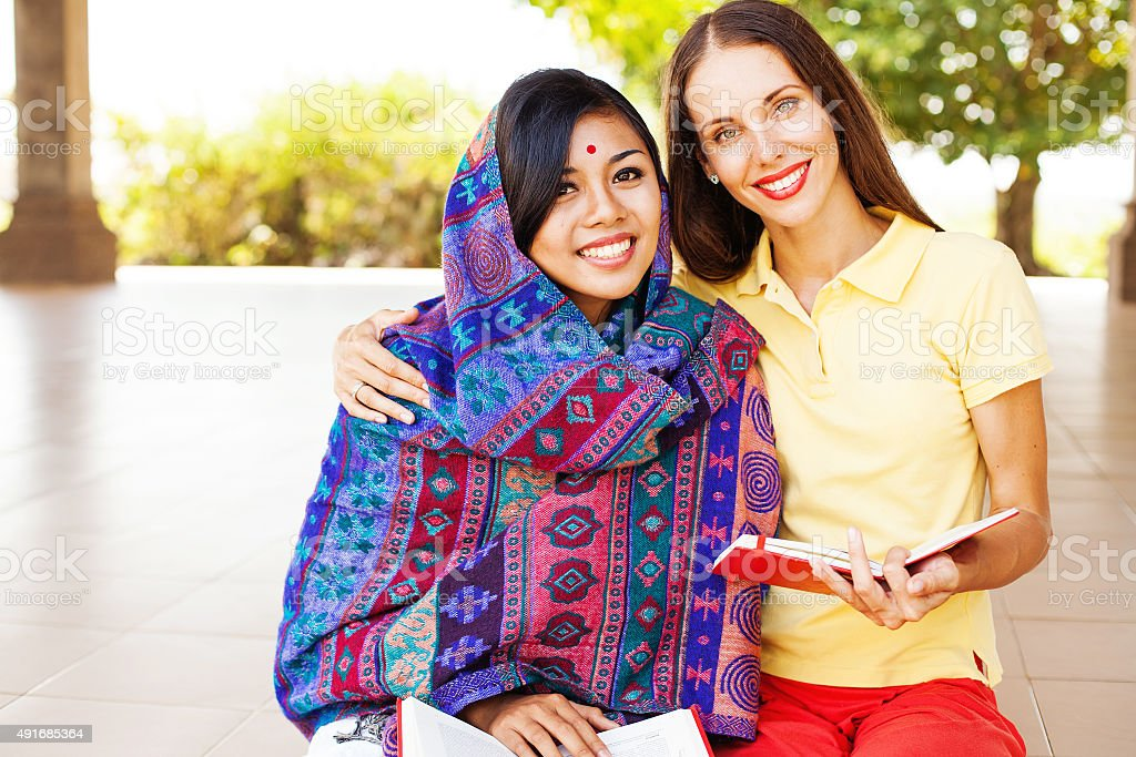 European woman and asian muslim women sitting on astreet stock photo