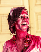 European woman covered in holi festival colours