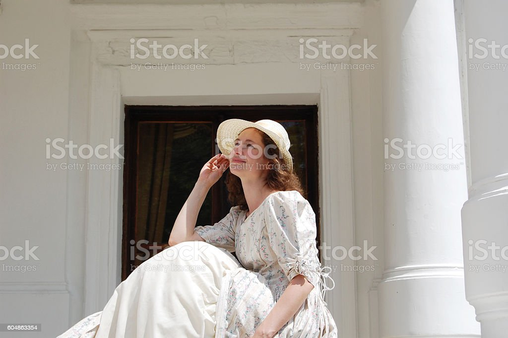 European woman touching hat in vintage dress near palace. stock photo