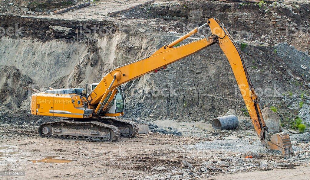 European yellow and orange excavator in action stock photo