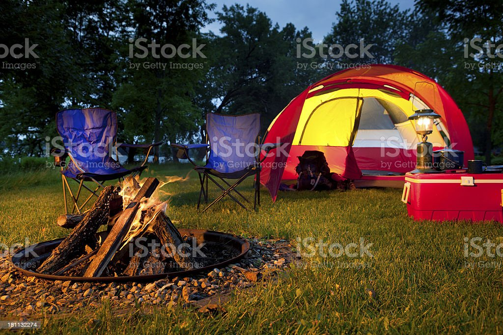Evening Campsite with Red Tent, Chairs, and Burning Fire Pit royalty-free stock photo