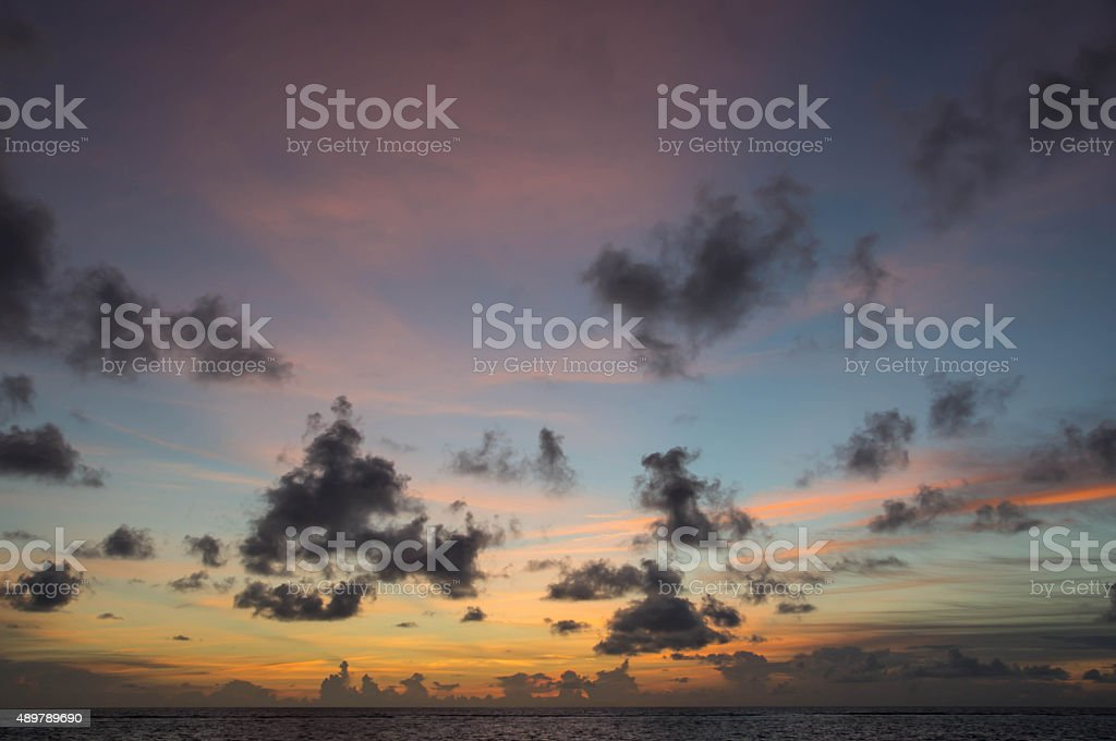 Evening cloudy sky over the ocean at sunset stock photo