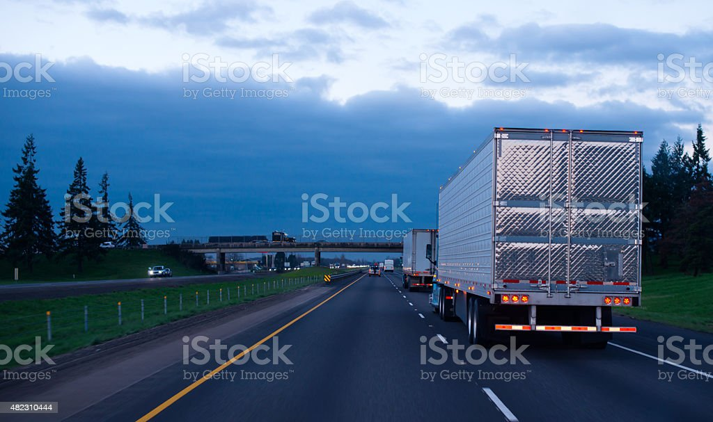 Evening convoy semi trucks trailers on straight interstate highway stock photo