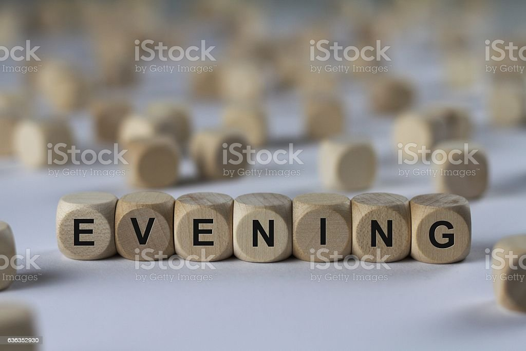 evening - cube with letters, sign with wooden cubes stock photo