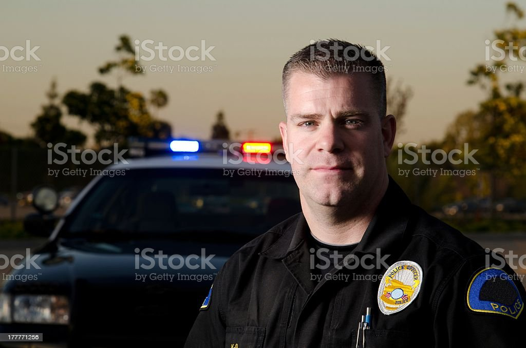Evening head shot of male police officer with car behind royalty-free stock photo