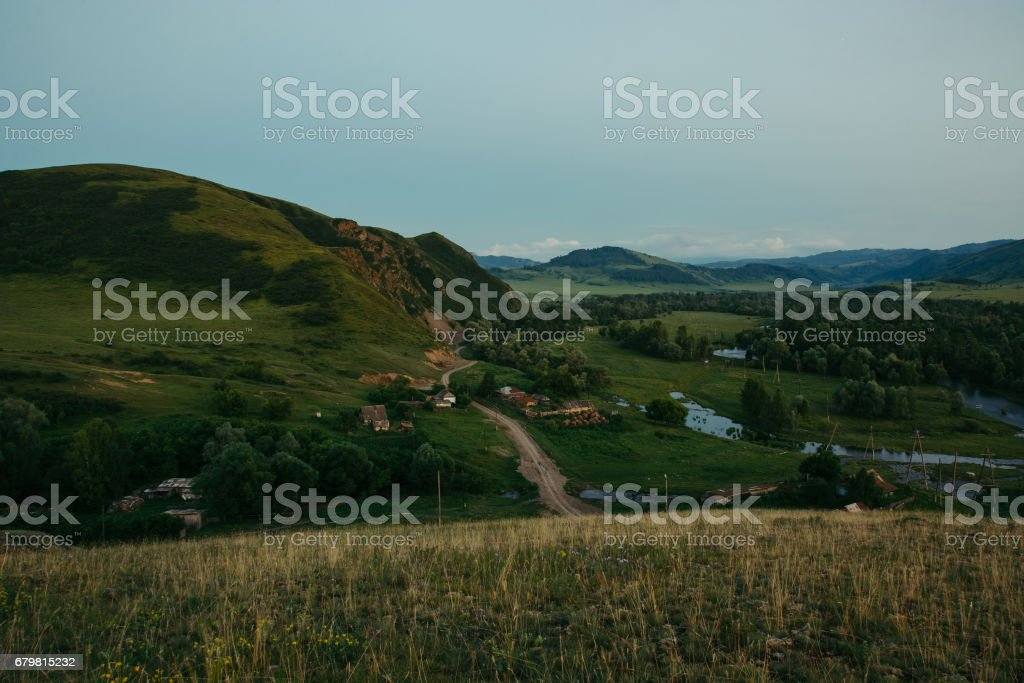 Evening landscape of the village built among the hills, forests and mountains. Interaction with the nature of Altai. stock photo