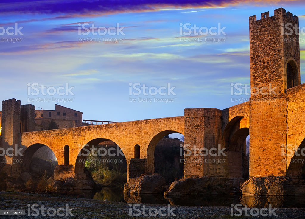 Evening photo of medieval bridge over river. Besalu stock photo