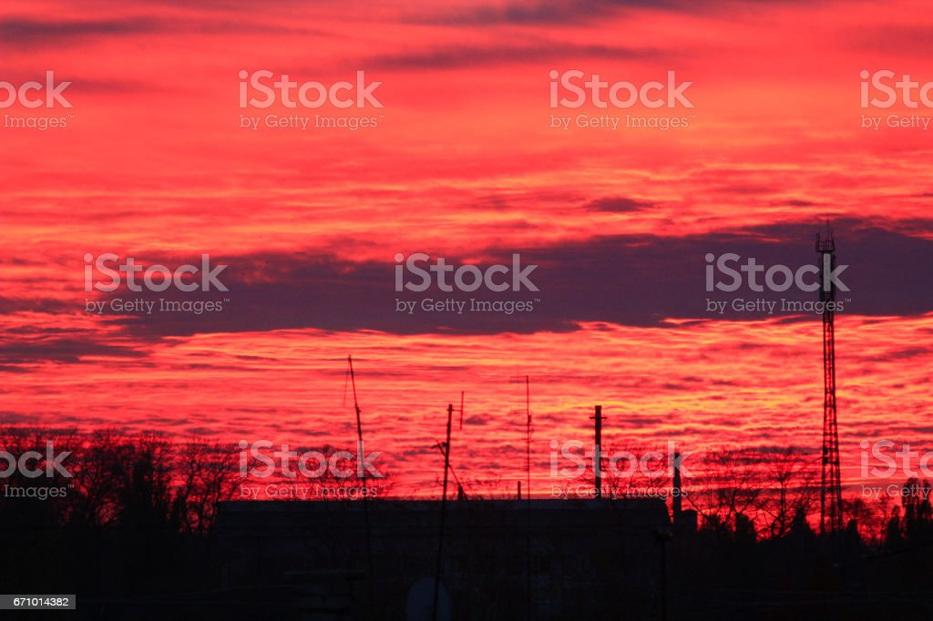 Evening scarlet sunset with beautiful picturesque clouds above the houses stock photo