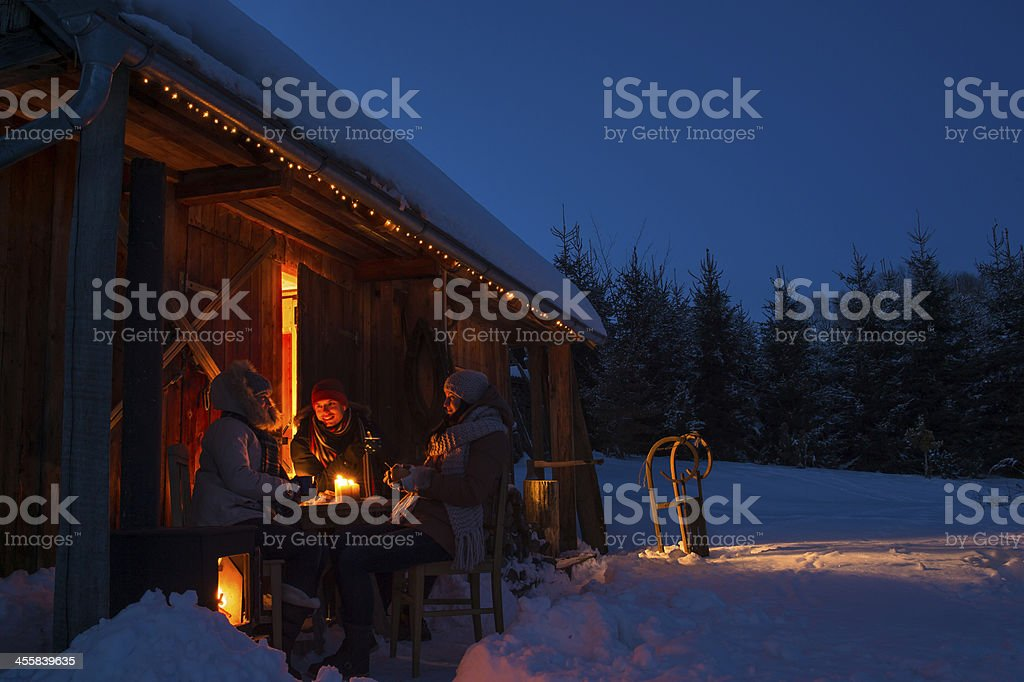 Evening snow winter cottage friends enjoy hot drinks stock photo