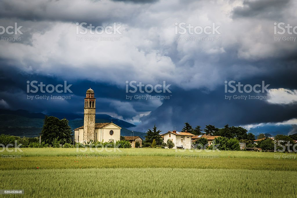 Evening storm over the medieval village stock photo