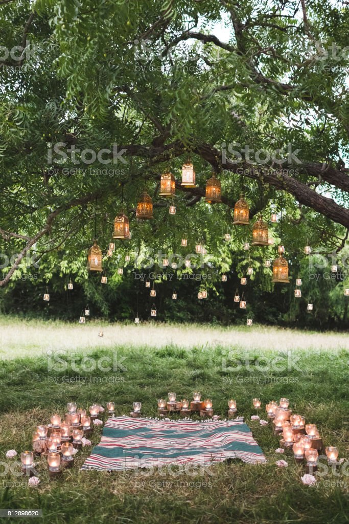 Evening wedding ceremony with a rug and lot of vintage lamps and candles on big tree. Rustic style stock photo
