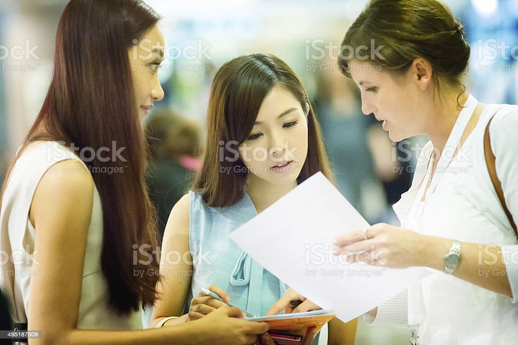 Event hostess offers help with registration stock photo