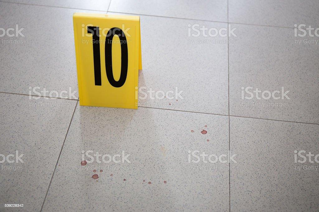 evidence marker at bloodstain on room floor in crime scene stock photo