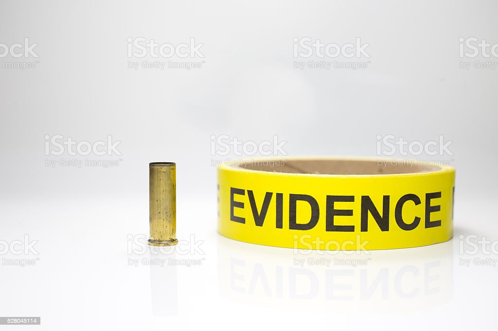 evidence tape with brass bullet case on white background stock photo