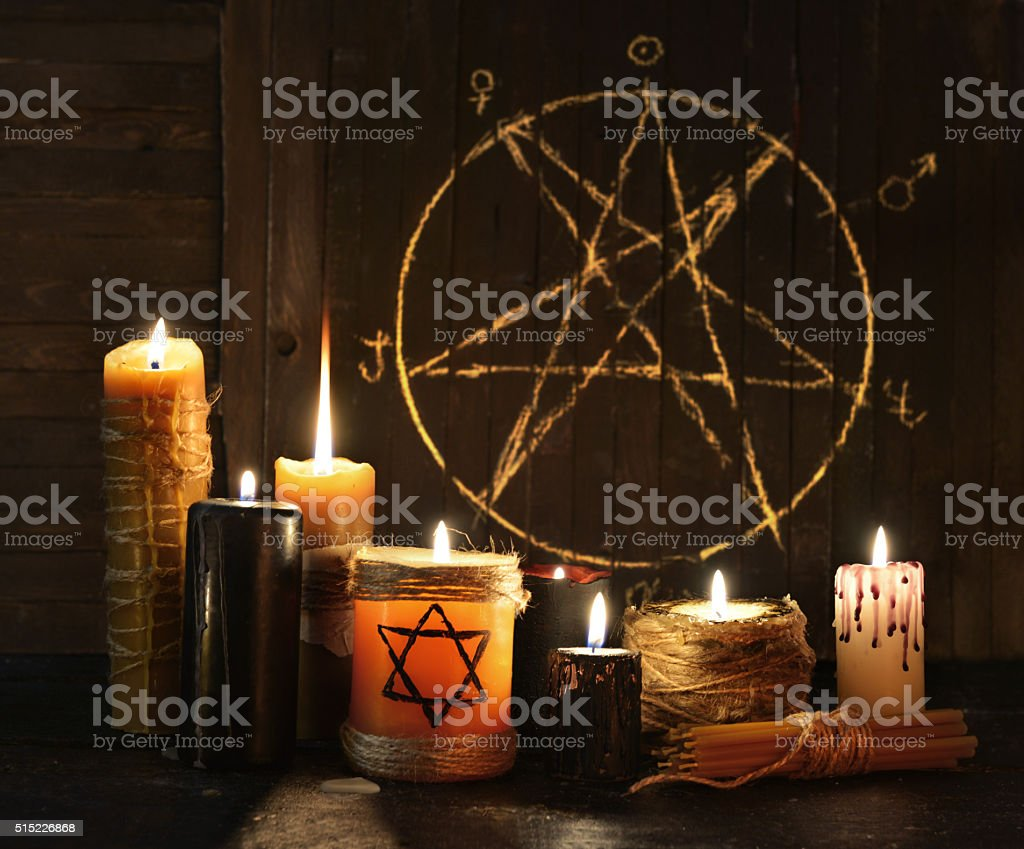 Evil candles against pentagram background stock photo