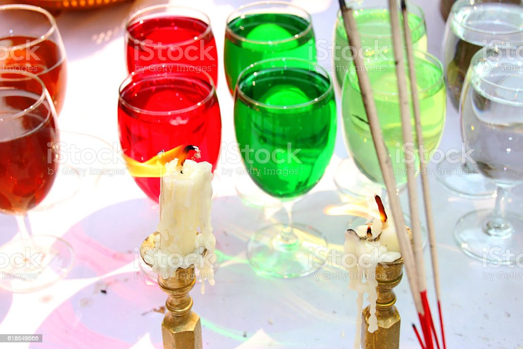 evil candles burning and color water in glasses background stock photo
