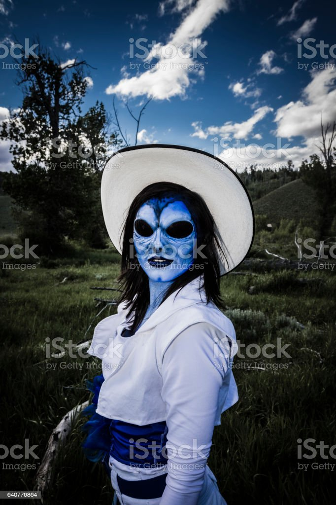 Evil Cowgirl Alien On A Ranch At Night stock photo