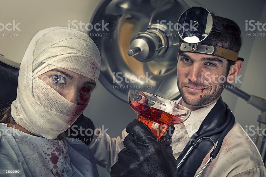 Evil Doctor drinking eyeball cocktail from shocked female victim stock photo